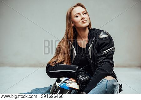 Cheerful And Cute Female Motorcyclist Poses Sitting On Floor With Her Helmet And Looking At Camear I