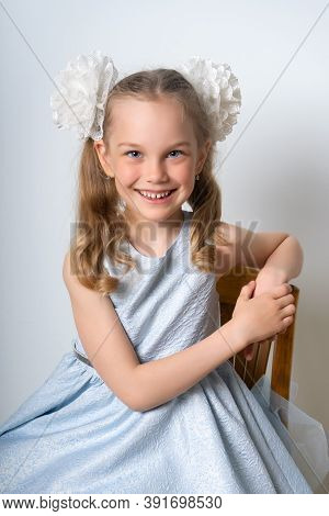 Portrait Of An Elegant Seven-year-old Girl In A Blue Festive Dress With Hairstyles With Bows, Leanin