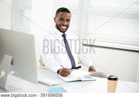 Happy handsome african american businessman smiling while looking at camera in office