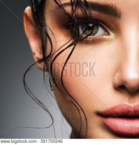 Closeup portrait of a beautiful young woman with fashion makeup. Smokey eye make-up. Face with a bang