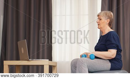 Senior Woman With Healthy Lifestyle Training Arms Using Dumbbells On Stability Ball. Online Training