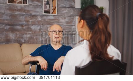 Senior Patient In Wheelchair Talking With Medical Worker. Disabled Disability Old Person With Medica