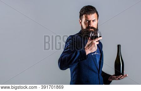Red Wine In Bottle, Wine Glass. Sommelier Man, Degustator, Winery. Man Holding Bottle With Champagne