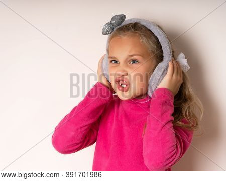 Little Cute Toothless Girl Is Surprised Pretending To Listen To Music In Warm Fur Headphones On A Li