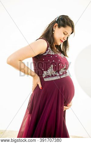 Young Pregnant Woman Looking At Belly Standing Against White Background Outdoor Studio Shot, Happy F