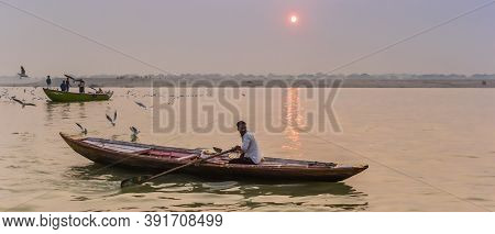 Varanasi, India - November 07, 2019: Panorama Of A Young Man In A Row Boat On The Ganges River In Va