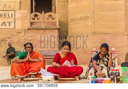 Varanasi, India - November 07, 2019: Colorful Women Sitting And Praying At The Ghats In Varanasi, In