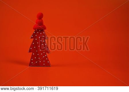 Christmas And New Year Festive Concept. Red Decorative Christmas Tree In A Red Knitted Hat On A Brig