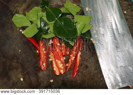 Preparation Of Sliced Red Peppers And Green Kaffir Lime Leaves On A Wooden Cutting Board For Cooking