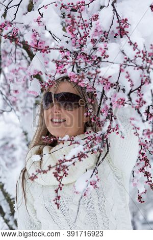Woman Stands Under Cherry Blossom Tree Blooming With Fresh Winter Snow
