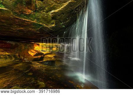 Waterfall Flowing Over A Cave In The Night,  The Inside Lit By Warm Light