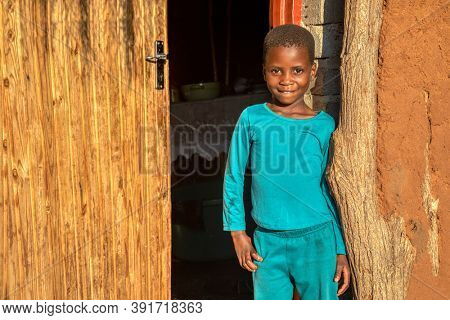 African village, child standing in front of the house in a sunny day