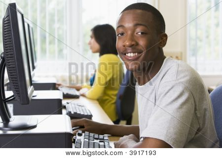 Student Sitting At A Computer Terminal With Woman In Background (Selective Focus/High Key)