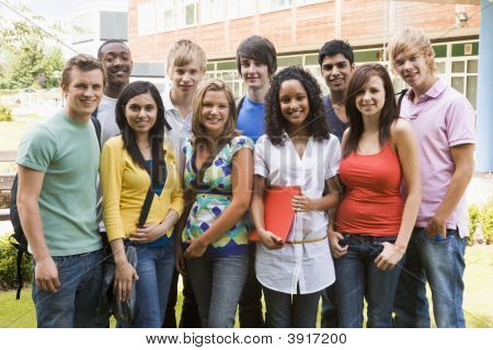 Group of students outdoors looking at camera smiling poster