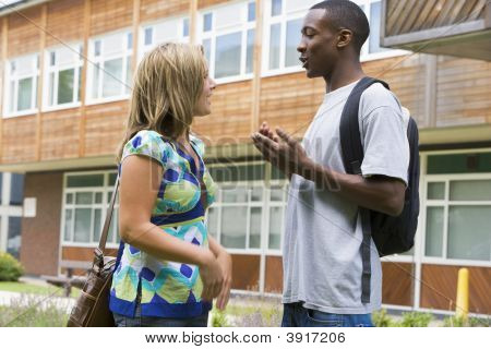 Two students standing outdoors talking poster