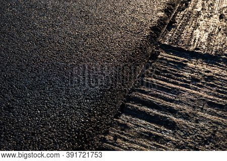 Freshly Laid Black Bitumen Asphalt With A High Edge To The Gravel Showing The Structure. Laying A Ne