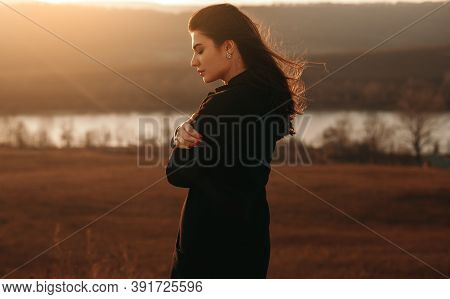 Side View Of Lonely Silent Young Brunette In Warm Clothes Standing Against Lake In Windy Autumn Day