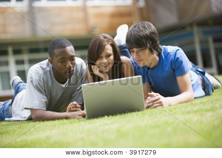Three students lying outdoors on lawn with laptop poster