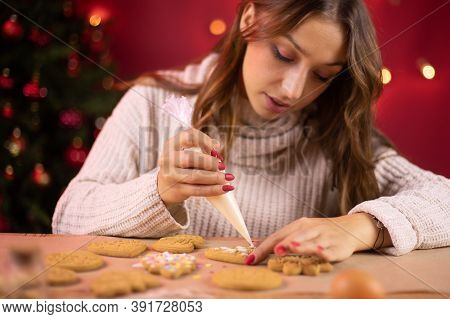 Christmas Bakery. Cute Brunette Girl Icing Christmas Gingerbread With Icing-sugar With Christmas Tre