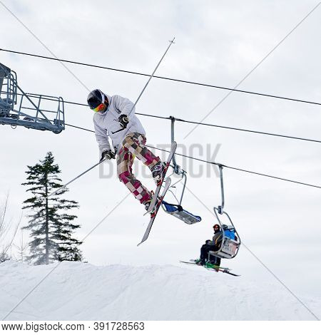 Man Skier Skiing Downhill With Cloudy Sky And Ski Lifts On Background. Male Freerider On Skis Making
