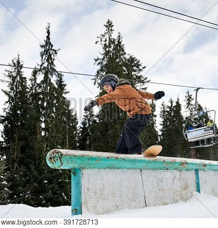 Male Snowboarder In Helmet Riding Snowboard Under Cloudy Sky And Ski Lifts. Man Performing Tricks Wi