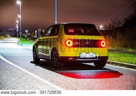 Prague, Czech Republic - October 26, 2020. Night Photo Of Back Side Of Honda E On Wet Road