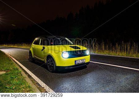 Prague, Czech Republic - October 26, 2020. Night Photo Of Electric Honda E On The Road After Rain