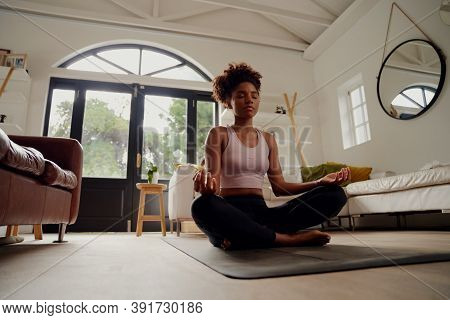 Low Angle View Of Beautiful Young Woman Sitting On Fitness Mat At Home In Lotus Position While Medit