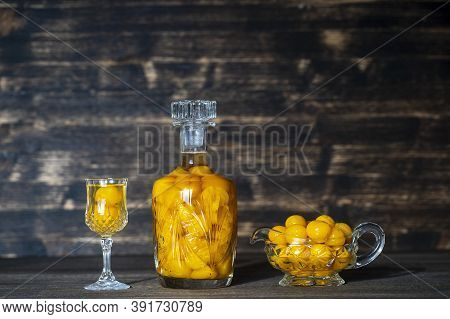 Homemade Tincture Of Yellow Cherry Plum In A Crystal Bottle And A Wine Crystal Glass On Wooden Backg