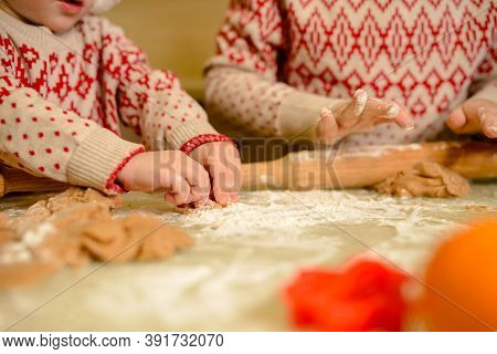 Child Hands Preparing Dough For Christmas Cookies. Close Up Of Childrens Hands Cutting Cookies Out.