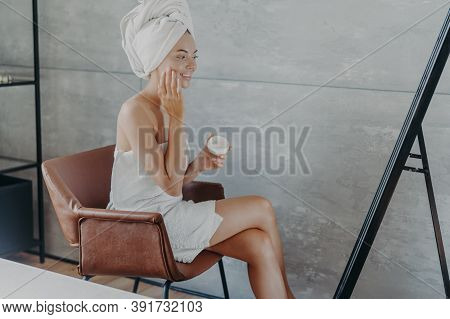 Skin Care Concept. Indoor Shot Of Pretty Smiling Woman Sits In Comfortable Armchair Opposite Mirror,