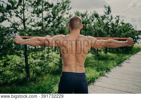 Back View Of Unrecognizable Sportsman Stretches Elastic Resistance Band, Demonstrares Strong Muscula