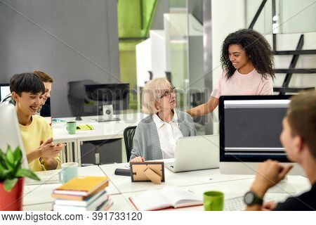 Aged Woman, Senior Intern Looking At Her Female Colleague While Completing First Task At Work, Frien