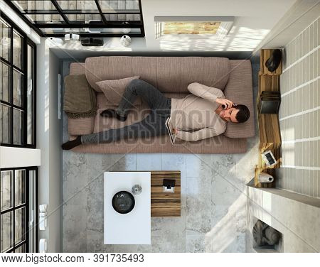 Man lying on couch at home, working from home with tablet, home office. above the head view.