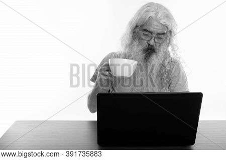 Studio Shot Of Senior Bearded Man Wearing Eyeglasses And Holding Coffee Cup While Using Laptop On Wo