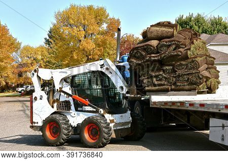 Moorhead, Minnesota, October 8, 2020: The Bobcat Skid Steer Lifting A Loaded Pallet Of Rolled Sod Is