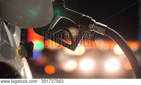 Fuel nozzle inserted in car's gas tank as it's being refueled at gas station pump at night. Closeup, shallow DOF.