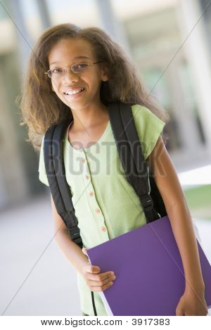 Student standing outside school holding binder and smiling (selective focus) poster