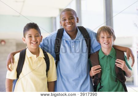 Three students standing outside school together smiling (high key) poster