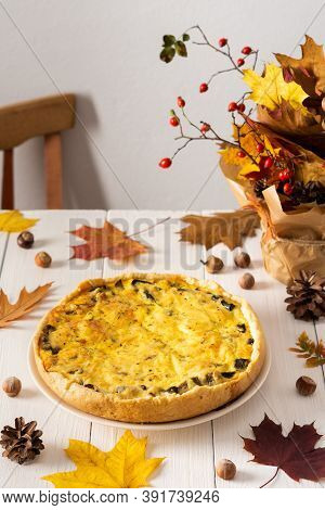 Quiche Pie With Mushrooms And Cheese, Autumn Background With Fallen Maple And Oak Leaves, Pine Cones