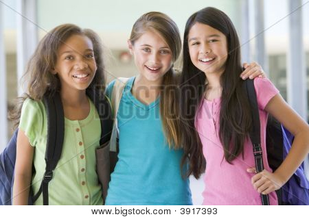 Three students standing outside school together smiling (selective focus) poster