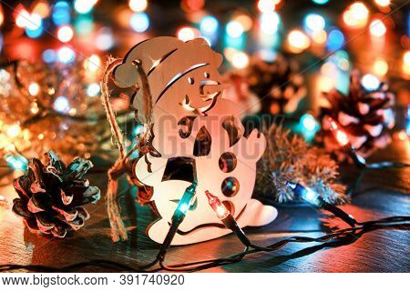 Christmas Background With Wooden Snowman Against The Backdrop Of Christmas Lights