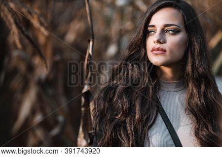Portrait Of A Beautiful Brunette Girl With Hazel Eyes. Side View