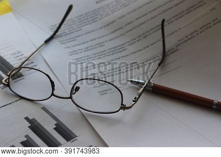 Business Legal Document Concept : Pen And Glasses On A Agreement Form