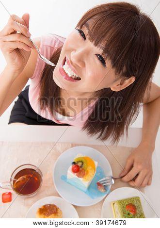 Fun Asian woman eating the cake inside house