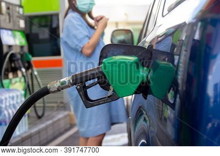 Blue Car At Gas Station Filled With Fuel. Closeup Woman Hand Pumping Gasoline Fuel In Car At Gas Sta