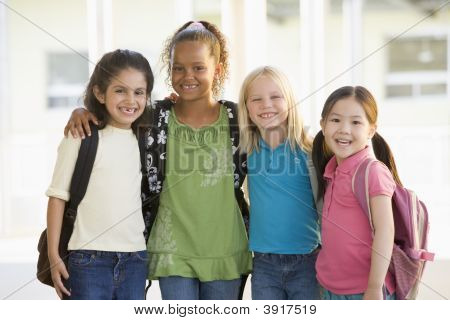 Four students outside school standing together smiling (high key) poster