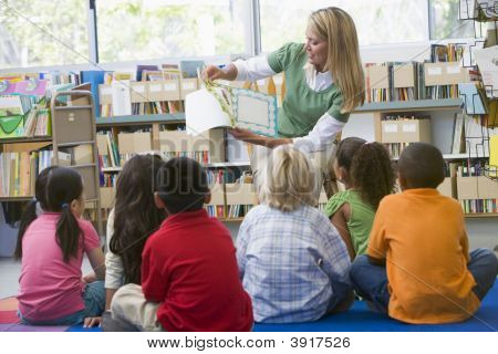 Teacher In Class Reading To Students