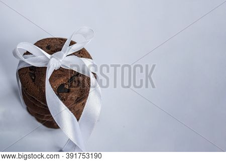 Stack Of Chocolate Chip Cookies With Chocolate Crumbs Wrapped In White Satin Ribbon On A Light Backg