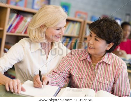 Two Women Sitting In Library With A Book And Notepad (Selective Focus)